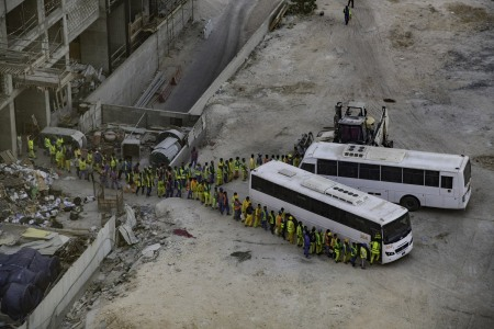 Immigrant workers line up to board the bus back to their compound after a days work